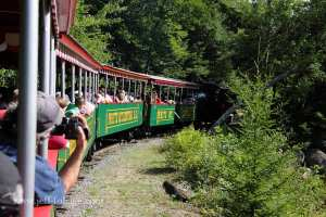 brightly colored train rounds the bend at Clark's trading Post in New Hampshire