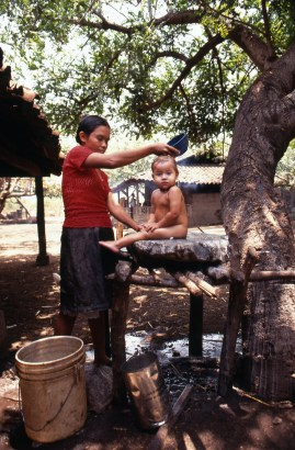 Young Mother Washing Her Child at Farm Coop near Leon
