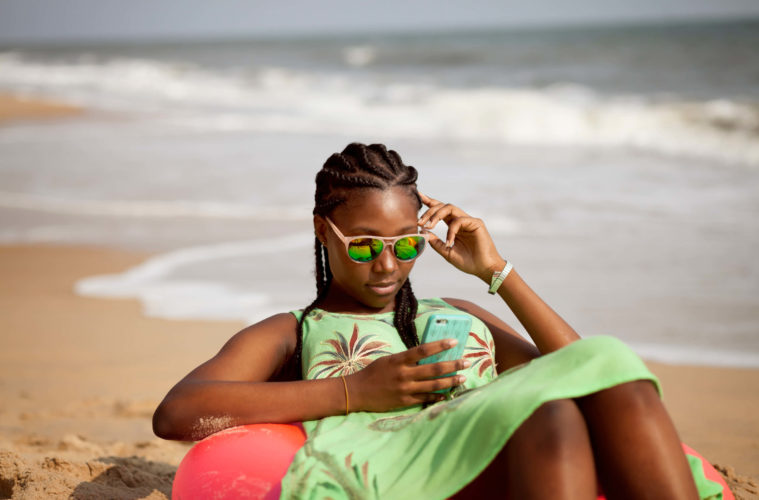Young-woman-looking-at-phone-by-the-beach-©JFP@PICHA1-759x500