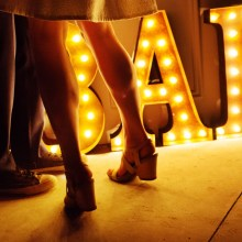 Retro bar sign lighting the bride and grooms legs.
