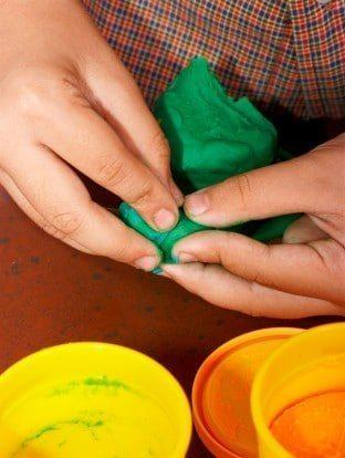 kid playing with play dough