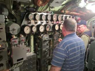 Former USS Requin crew member studies equipment on a behind-the-scenes tour of the cold-war era submarine docked at the Carnegie Science Center.