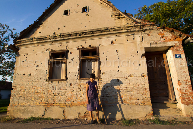 Woman poses for a photograph outside her house riddled with bullets from the war. Tovarnik. Croatia. © Jess Hurd/reportdigital.co.uk Tel: 01789-262151/07831-121483   info@reportdigital.co.uk   NUJ recommended terms & conditions apply. Moral rights asserted under Copyright Designs & Patents Act 1988. Credit is required. No part of this photo to be stored, reproduced, manipulated or transmitted by any means without permission.