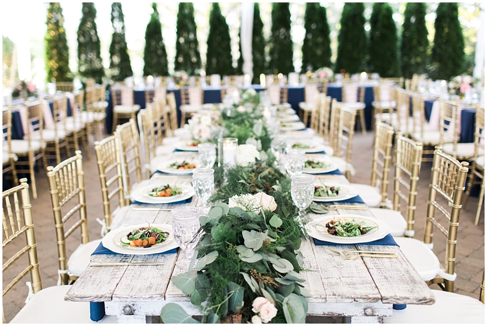 rustic wedding tablescape; farmhouse wedding table; bridal party head table; draped greenery; navy napkins; gold flatware; gold chiavari chairs; southern wedding; creative business recap; our year in review | Ivan & Louise Images