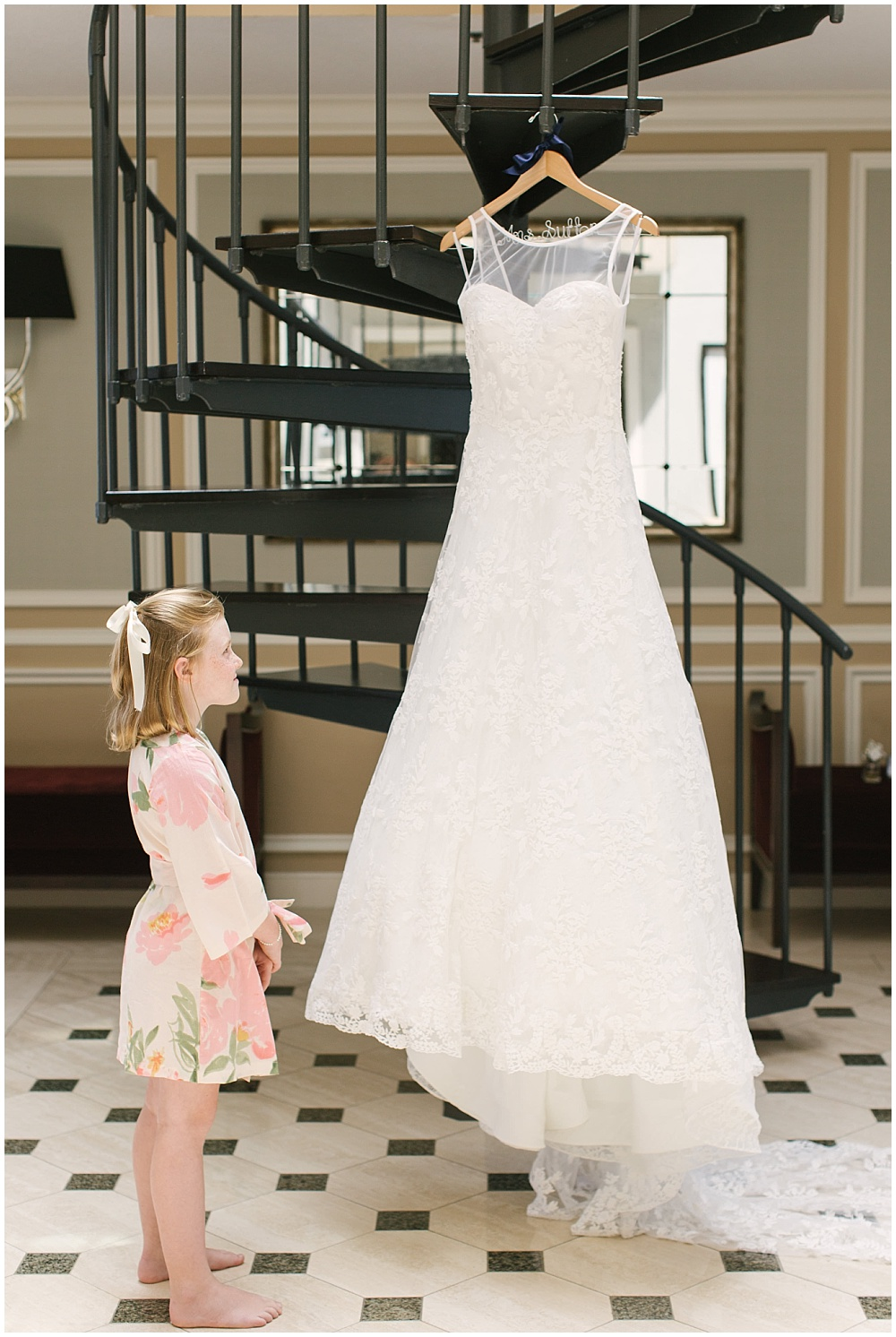 flower girl with bride's dress; floral flower girl robe; white wedding dress; wooden hanger; Navy + blush wedding; Scottish Rite Cathedral Indianapolis | Traci & Troy Photography and Jessica Dum Wedding Coordination