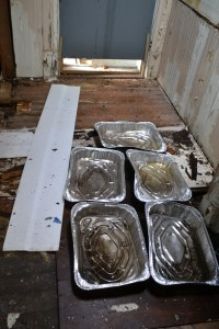 Foil turkey roasting pans catch water from the open roof in the master bathroom.