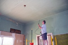 Spraying the beadboard ceiling with cleaning mixture. This 106 year old ceiling is in great shape.