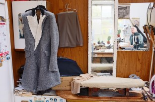 The tailor's workshop, with a partly contstructed double breasted Harris Tweed overcoat/jacket hanging on the wall.