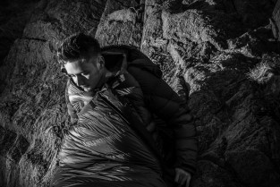 COMMERCIAL PHOTOGRAPHER - An outdoors model in a keeping warm in a sleeping bag