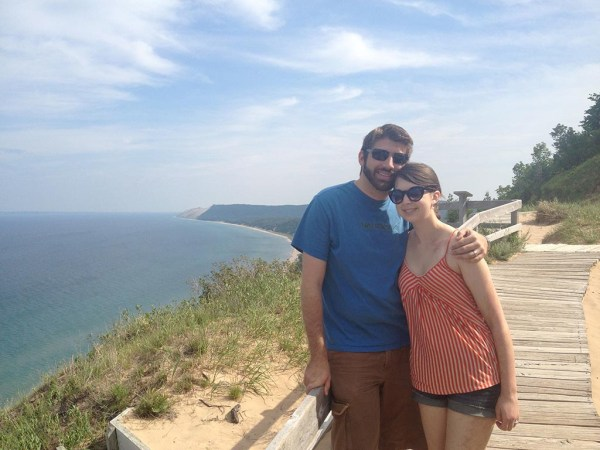 the happy couple posing next to lake michigan