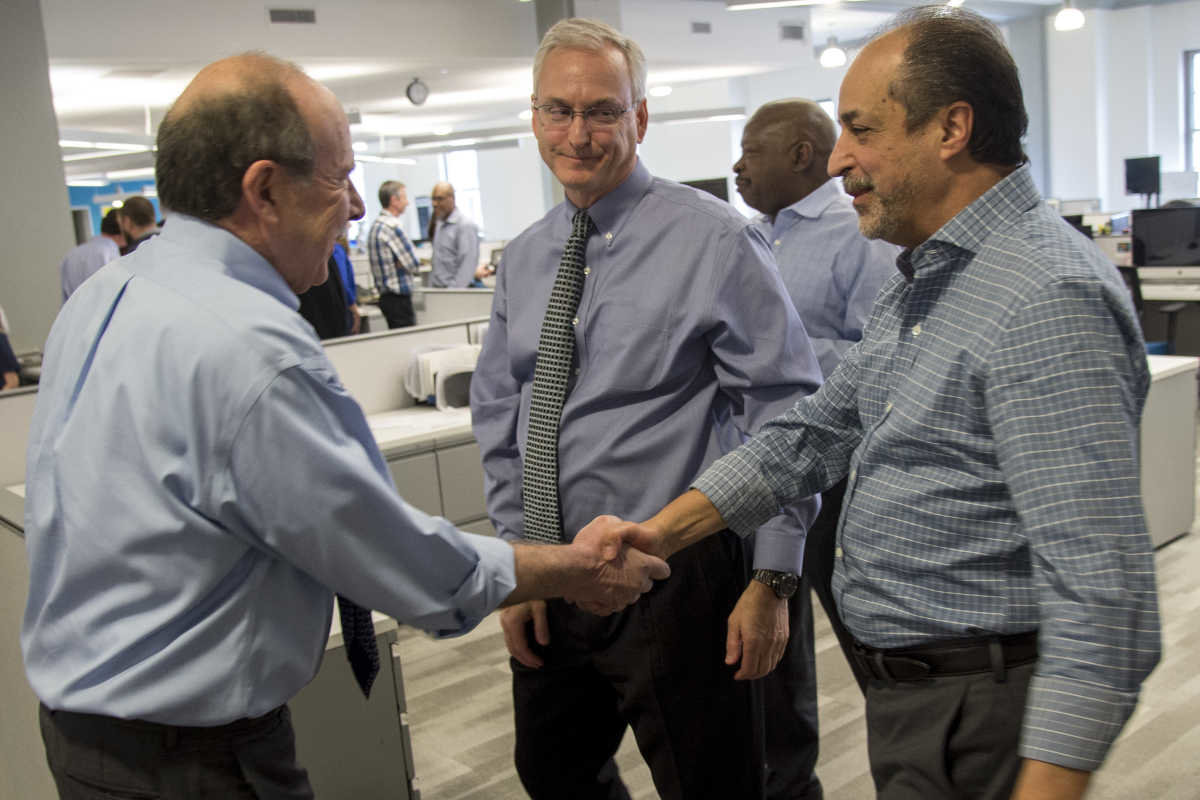 Gabriel Escobar, right, accepts congratulations from Philadelphia Inquirer editor William K. Marimow after Stan Wischnowski, executive editor and senior vice president of the Philadelphia Media Network, center, announced that Escobar is being promoted to the new position of PMN editor and vice president. Michael Days, in background, becomes PMN editor for reader engagement. (Credit: Clem Murray/philly.com)