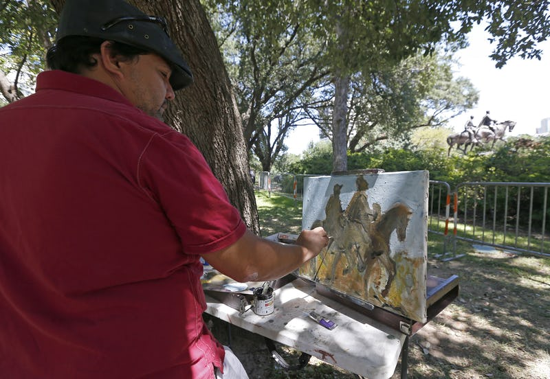 "Artist Jerrel Sustaita works on his painting of the Robert E. Lee statue at Robert E. Lee Park in Dallas on Thursday. He said, ""I might not be able to do it tomorrow."" (Credit: Jae S. Lee/Dallas Morning News)"