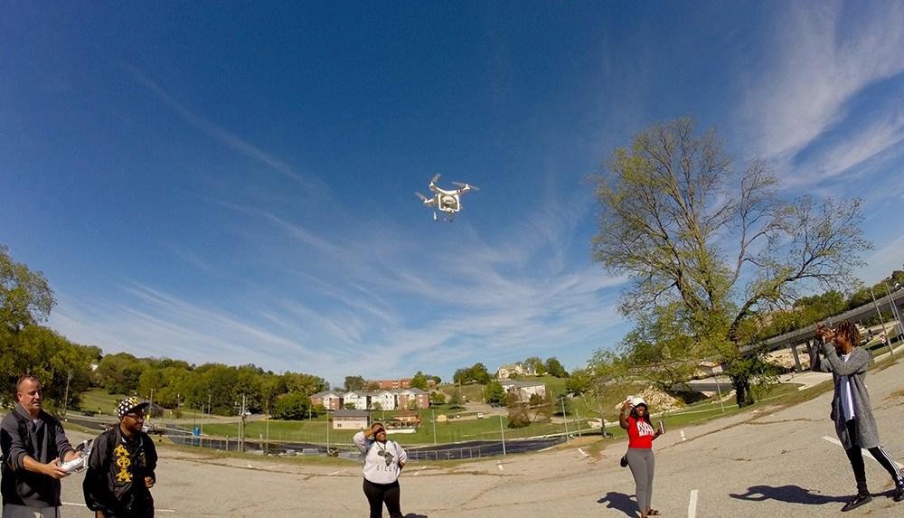 Lincoln University journalism students observe as assistant professor Will Sites, left, pilots a DJI Phantom 3 drone. (Credit: Kelsey Bias)