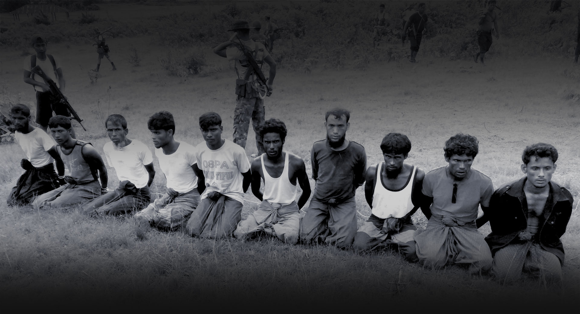 """Reuters reported, """"This photo was taken on the day the 10 Rohingya men were killed. Paramilitary police officer Aung Min, left, stands guard behind them. The picture was obtained from a Buddhist village elder, and authenticated by witnesses."""""""