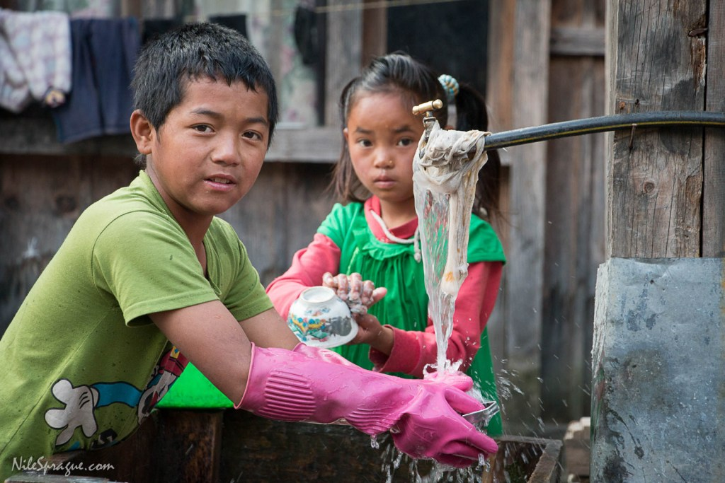 Boy and girl wash dishes in Danaque Village, Manang District.
