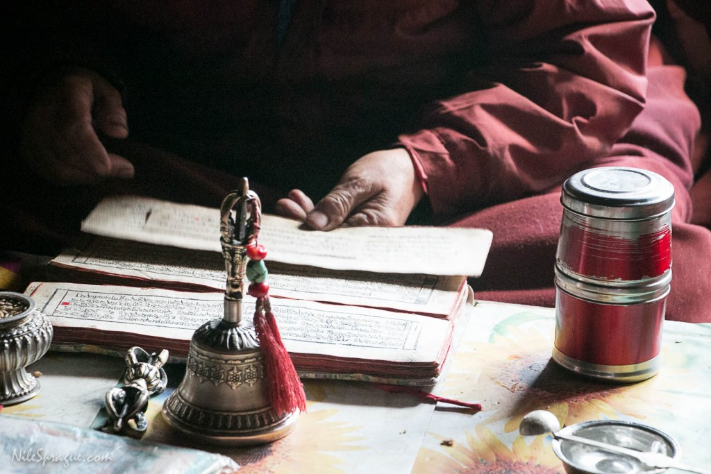 The hands of a Buddhist monk holding pages from an ancient prayer book on the last day of an eight day puja, Royal Mustang Hotel, Ghemi, Upper Mustang. The prayer book is printed with hand-carved blocks on paper called pecha. In the foreground are two ceremonial instruments: a brass bell and dorje. This puja ceremony is held annually for prosperity and good luck, during which numerous monks gather to chant prayers throughout the day. The dorje is held in the right hand and represents the male principle: action or means. The bell is held in the left hand and represents the female principle: wisdom.