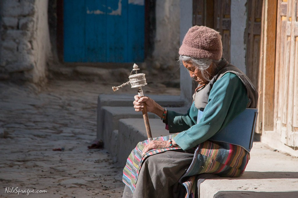 Elderly Tibetan woman spinning prayer wheel as she sits in the afternoon sun, Lo Manthang, Upper Mustang. Prayer wheels are filled with prayers and mantras, thus sending them out into the world in much the same way as prayer flags. Each afternoon, as I walked the streets of Lo Manthang, I would see this grandmother seated in the sun, deep in meditation with her eyes closed, spinning her prayer wheel.