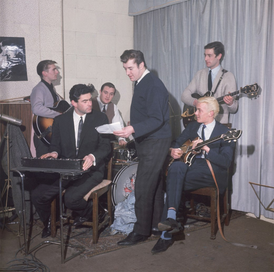 English instrumental pop group The Tornados (guitarists Alan Caddy (1940 - 2000) and George Bellamy, drummer Clem Cattini, keyboard player Roger Lavern and bass player Heinz Burt (1942 - 2000) with producer Joe Meek (1929 - 1967, centre) at Meek's studio in Holloway, London, circa 1962. The Tornados were the house band at the studio, and are best known for their hit with Meek's 'Telstar'. (Photo by John Pratt/Keystone/Hulton Archive/Getty Images)