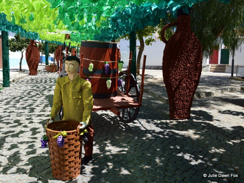Paper figurine of a man collecting grapes in a tall basket.