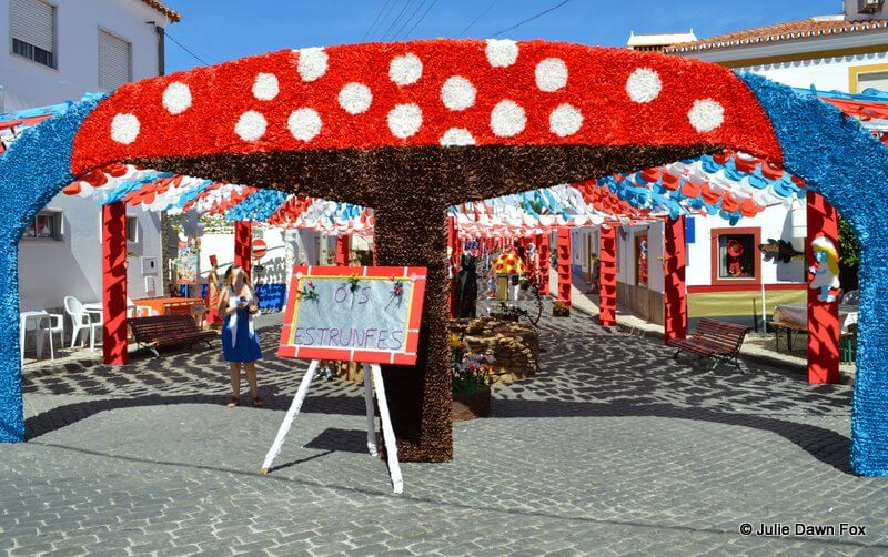Red and white toadstool made from coloured tissue paper forming the entrance to a decorated street.