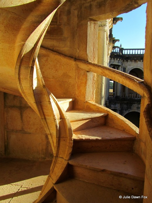 Bright, golden sunlight on spiral stone staircase