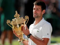 Tennis - Wimbledon - All England Lawn Tennis and Croquet Club, London, Britain - July 15, 2018  Serbia's Novak Djokovic celebrates with the trophy after winning the men's singles final against South Africa's Kevin Anderson.    REUTERS/Andrew Couldridge