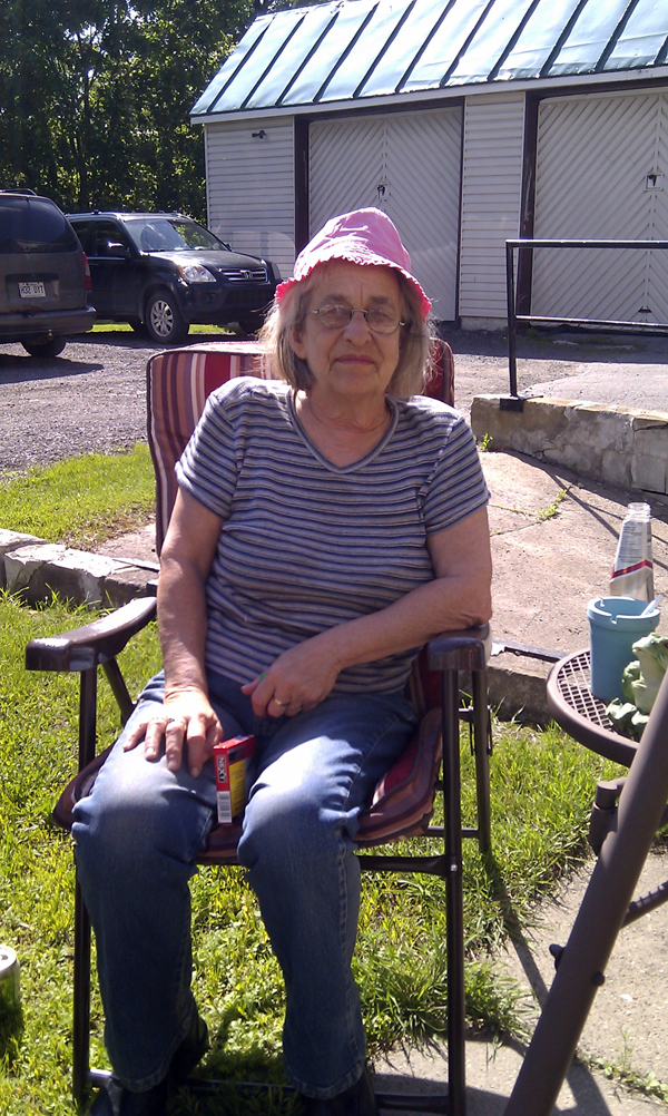 My mom at our cousin's house (wearing my niece's hat)