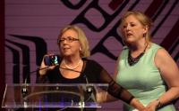 Lisa Raitt (jobboldal) próbálja lehozni a botrányt okozó Mayt a színpadról. Fotó: Képkocka a CBC videójából.