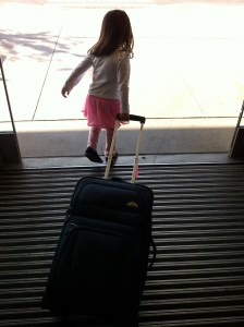 little girl in an airport with a suitcase