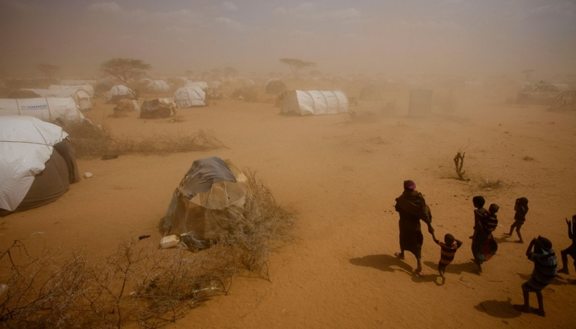 A mother walks with her children through a dust storm to their newly erected tent in the new arrivals area of Dagehaley camp. Kate Holt.