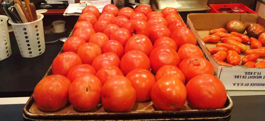 A photograph of a large tray of tomatoes.
