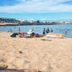 A sandy beach with people sunbathing