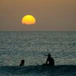 ocean sunset and two surfers