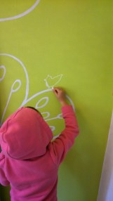 Chalking and painting on the wall from her own design.