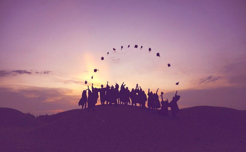 Studens throwing their graduation caps to form a semicircle in the air in front of a sunset.