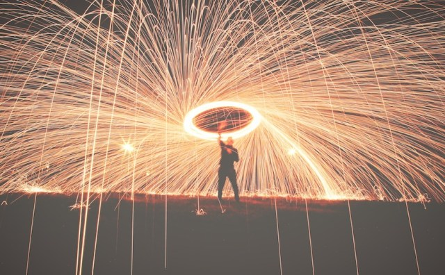 Man holding a spinning sparkler with a long exposure to appear like a network of sparks.