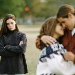Teenage girl (17-19) watching couple embrace (focus on girl)