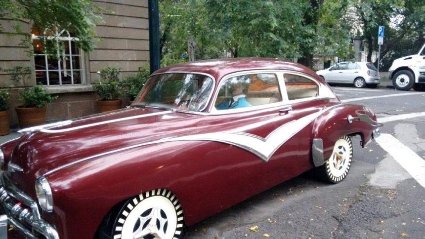 Un auto clásico con un maniquí dentro