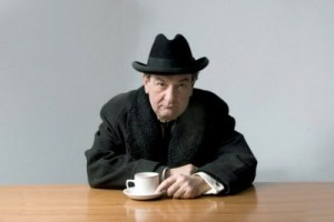 Ken Stott as Hancock - sitting at a table holding a cup and wearing a black coat and hat