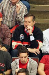 Ricketts watches the Hawks win wearing a jersey over his business shirt.