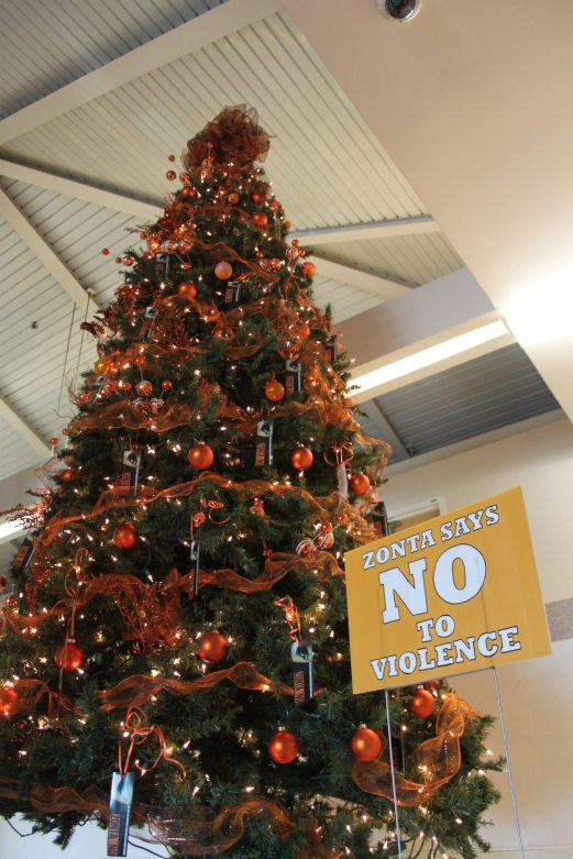 Zonta's tree, a very tall specimen covered with orange decorations, proclaims the club's message for the month: Zonta Says No to Violence.
