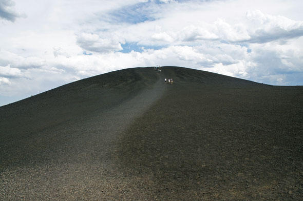 Visitors hiking a volcanic cone.