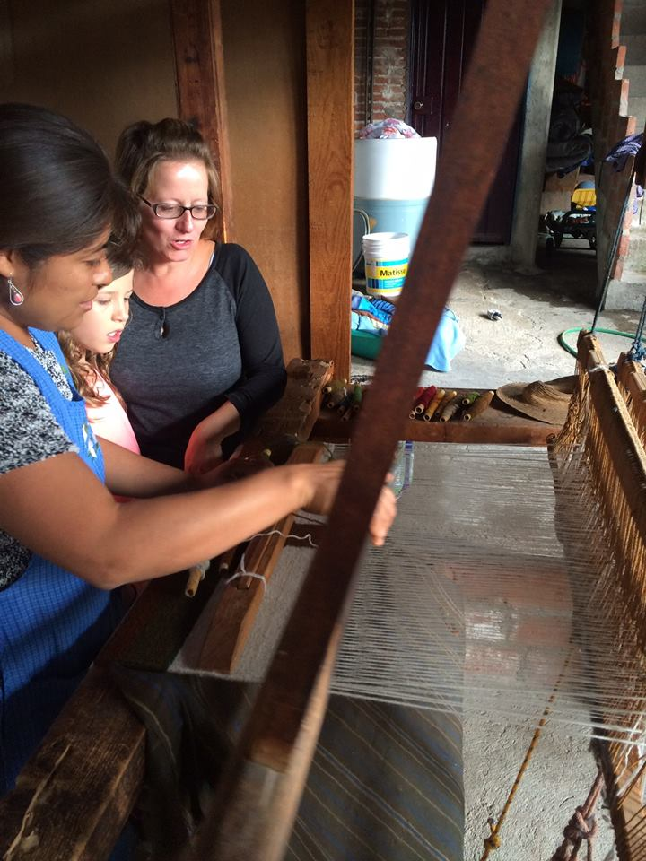 Riley learning how to weave from one of the younger generation of weavers, aided by an En Via guide.