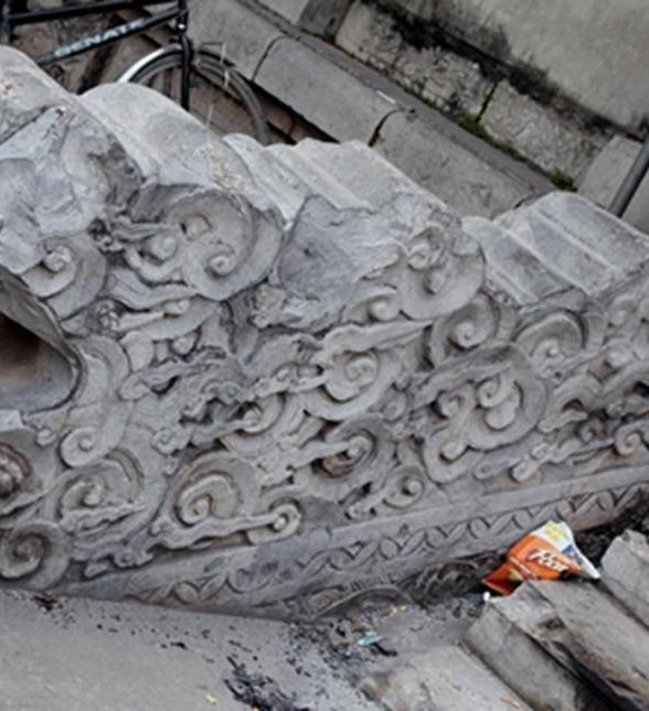 Rồng chầu được tạc cách điệu từ hình mây trong tình trạng vứt vỡ và mòn, có đôi chỗ còn bị mòn nhẵn thín.