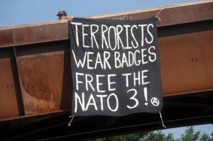 Banner Drop: Terrorists Wear Badges. Free the NATO 3!