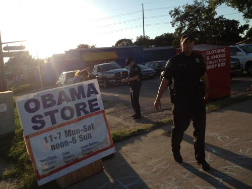 Police force a photographer back as Kit O'Connell is detained for chalking at the Austin Obama Store.