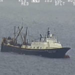 The factory trawler Alaska Juris lists to port in this still from a U.S. Coast Guard video. One of three inflatable liferafts can be seen near the Juris' bow.