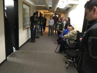 Father Innocent Dresdow turns into the room where the remains are being held and continues his prayer. Attendees, including descendants and museum staff, stand in the hall located in the museum's lower level. Kayla Desroches/KMXT