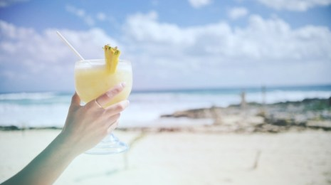 woman-holding-cocktail-drink-on-beach