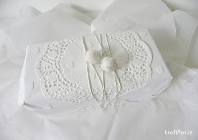 White kraft paper, doillie, white leather cord and pompoms with thin floral wire